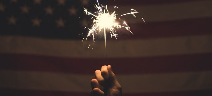 Hand holding sparkler in front of American flag